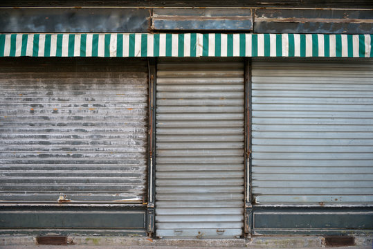 Old store. Ancient storefront with metallic closed curtains. Abandoned shop business.