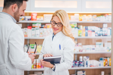 Smiling female pharmacist beggining to work at modern pharmacy, colleague giving her prescription book.