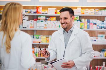 Male pharmacist talking to his female trainee.
