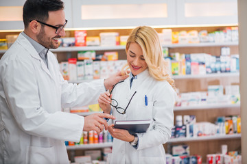 Handsome pharmacist talking to his intern in modern pharmacy.