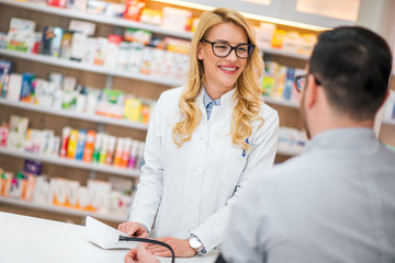 Friendly pharmacist and customer at drugstore.