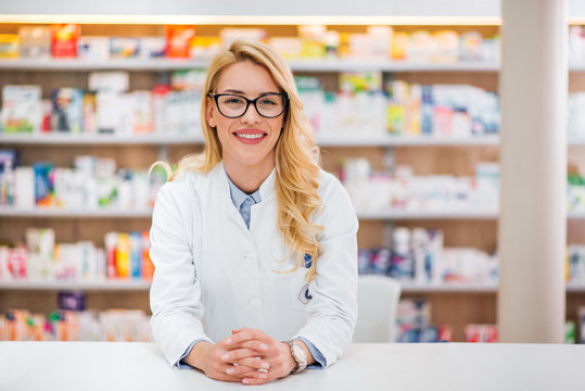Portrait of a beautiful blonde pharmacist leaning on counter at pharmaceutical store.