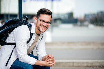 Portrait of a casual millenial traveler man waiting for a bus, smiling at camera.