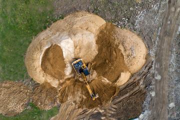 Crawler excavator builds a mound of soil.