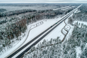 Freeway passing through the winter forest. The road goes away to the horizon line. Along the highway is a parking lot.