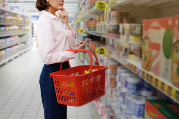 Asian woman with food basket thinking buy items at supermarket