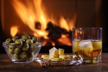 A glass of whisky and plate with cheese, olives and nuts