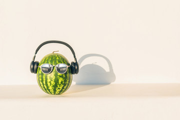 Creative and summer picture of watermelon in the form of a human head in the sunglasses and headphones on the white wall background.  concept