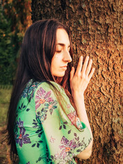 Beautiful caucasian brunette girl dressed in a dress with a floral pattern leaned against a tree with closed eyes in the forest at sunset. Unity with nature. Meditator