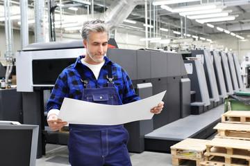 Fototapeta Drukarnia offsetowa. Drukarz z arkuszem wydruku stoi przed maszyna drukarską. obraz