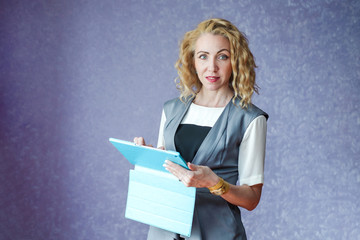 Young woman on a purple background in a gray suit and white blouse holding a tablet computer