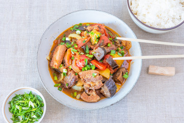 Fried pork with eggplants and sweet peppers in a large bowl and a cup of rice - a traditional Asian dish