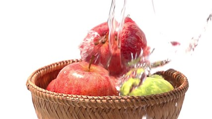 Fototapete - Pouring water on the red and the green apples in a bamboo basket on white background in Slow Motion
