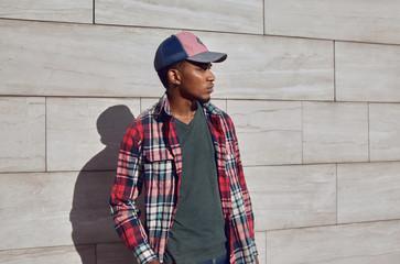 Wall Mural - Stylish african man wearing red plaid shirt, baseball cap, looking away, young guy posing on city street, gray brick wall background