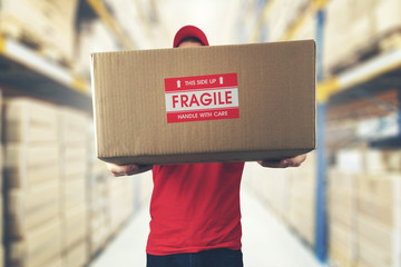 logistics warehouse worker holding package with fragile items