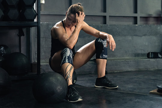 the girl after a crossfit workout wipes the sweat from face. rest after training. professional athlete in the gym