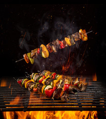 Tasty skewers on iron cast grate with fire flames.