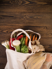 Fresh vegetables in bio eco cotton bags on old wooden table. Zero waste shopping concept. Plastic free.