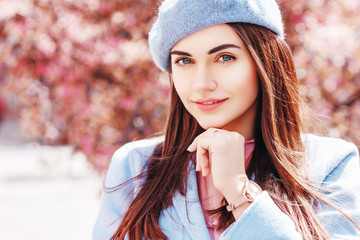 Outdoor close up portrait of  young beautiful happy smiling lady wearing stylish pastel blue color beret, coat, wrist watch, posing in spring street of European city. Copy, empty space for text