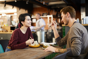 Side view portrait of cheerful young couple enjoying Asian food in restaurant, copy space