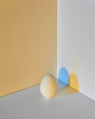 Painted egg on a gray-yellow double background with a reflection of blue-yellow shadows and copy space for text. Easter layout