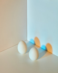 The composition of eggs on a gray-blue double background with copy space and multicolored shadows. Easter concept.