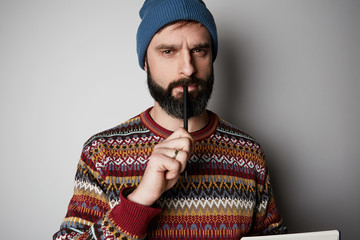 Young thoughtful bearded man in blue beanie thinking about test over empty background