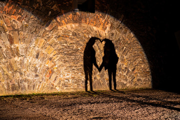 Two people project heart shaped shadow on the wall
