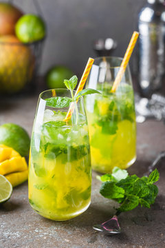 Fresh mango mojito cocktail with lime and mint in a glass