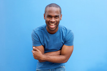 handsome young african american man laughing with arms crossed