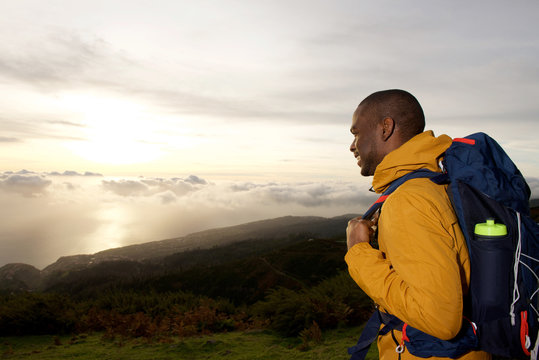 happy african american hiker looking at view from mountain