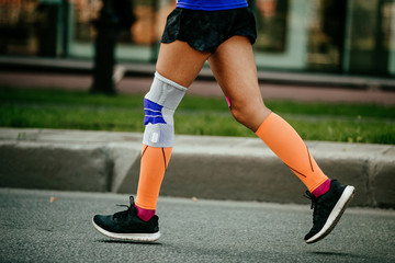 Wall Mural - women feet in compression socks and kneepad on knee running