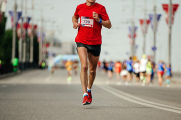 Fototapete - athlete runner in red t-shirt running marathon on city street