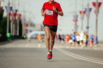 Wall Mural - athlete runner in red t-shirt running marathon on city street