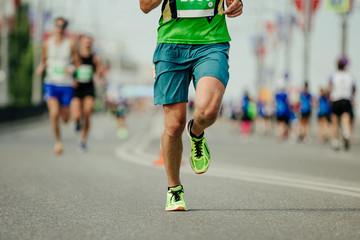Wall Mural - athlete runner in green sportswear running marathon race on city