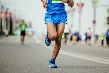 Fototapete - athlete runner in blue sportswear running marathon race on city