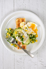 Savory waffles with fresh vegetable salad, avocado and egg on white background. Flat lay, top view, copy space.