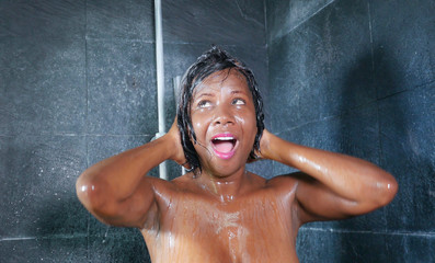 domestic lifestyle portrait of young happy and beautiful black African American woman smiling happy taking a shower at home bathroom washing her hair with shampoo