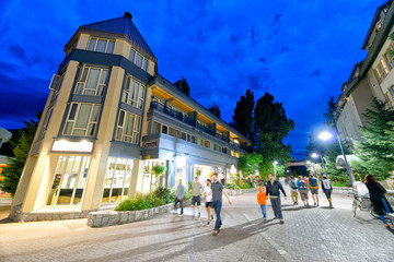 WHISTLER, CANADA - AUGUST 12, 2017: Tourists visit city center on a summer night. Whistler is a famous mountain destination in British Columbia