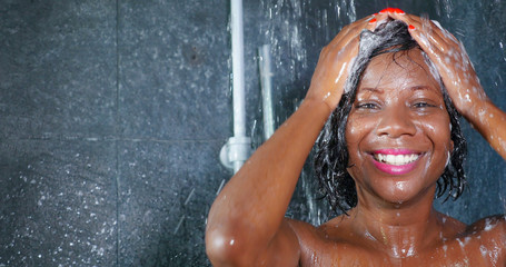 domestic lifestyle portrait of young happy and beautiful black afro American woman smiling happy taking a shower at home bathroom washing her hair with shampoo