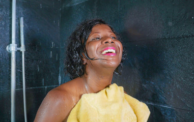lifestyle portrait of young beautiful and happy black African American woman smiling happy and cheerful drying hair and body with towel after having a shower