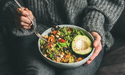 Poster de jardin Nourriture Healthy vegetarian dinner. Woman in jeans and warm sweater holding bowl with fresh salad, avocado, grains, beans, roasted vegetables, close-up. Superfood, clean eating, vegan, dieting food concept