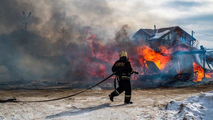 Firemen extinguishes a burning old wooden residential house. Firefighters at work on the fire. Fireman with a hose puts out the fire with water