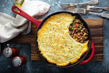 Shepherds pie with ground meat, vegetables and potatoes in a cast iron pan top view