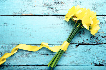 Photo sur Plexiglas Narcisse Yellow narcissus flowers on blue wooden table