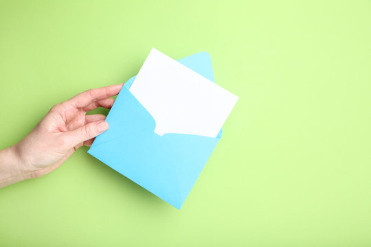 Female hand with paper envelope on green background