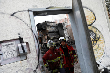 Firefighters are seen inside a burnt electrical substation after a massive blackout in Caracas