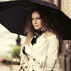 Sad beautiful fashion woman with umbrella on city street