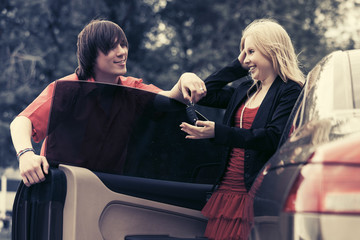 Happy young couple with a new car outdoor