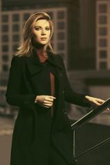 Fashion blonde business woman in black coat walking on city street